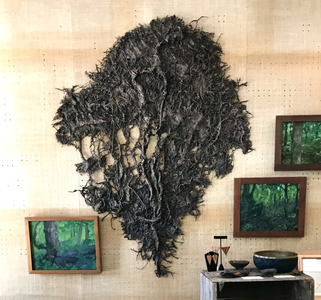 Full view of a fabric sculpture by MJ Seal that resembles a giant gray sea fan hanging on the wall at The Virginia Farmhouse