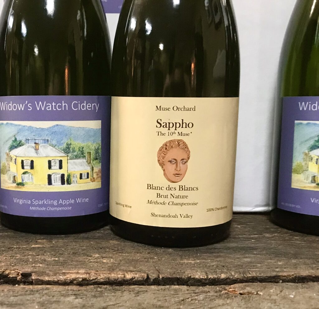 "Bottles of ""Sappho"" a sparkling white wine from Muse Orchard and Virginia Sparkling Apple Wine from Widow's Watch Cidery available for sale at The Virginia Farmhouse"