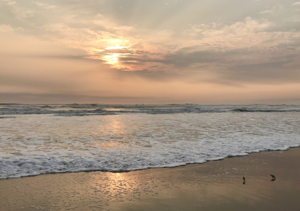 A peachy sunrise filtered through pearly gray clouds above the surf at Corolla, NC photographed by MJ Seal