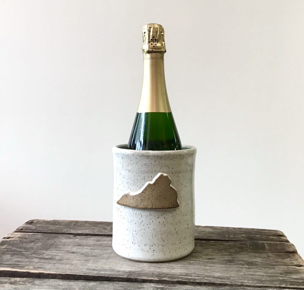 A white Ceramic Wine Chiller with a Virginia shaped ornament hand made locally by Barbarah Robertson available exclusively at The Virginia Farmhouse