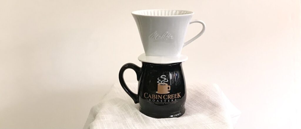 A ceramic pour over coffee brewer on a Cabin Creek Roasters mugavailable for sale at The Virginia Farmhouse