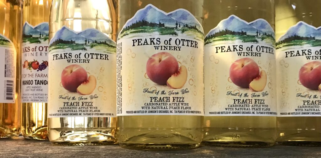 Bottles of Peach Fizz a sparkling peach wine from Peaks of Otter Winery available for sale at The Virginia Farmhouse